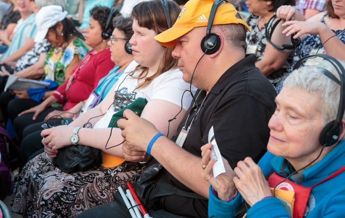 A group of Audio Description patrons at the Muny wearing headphones
