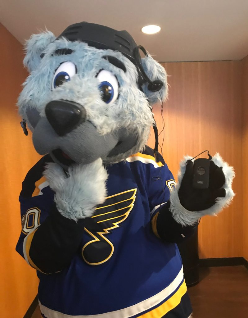 Louie, the Blues Mascot, holds an audio description device with a headset over one large ear.