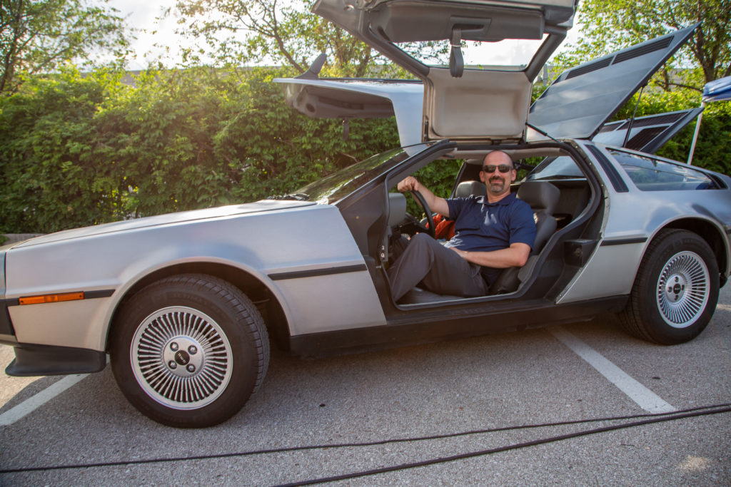 Chad Dillon sits inside a Delorean with both gullwing doors open