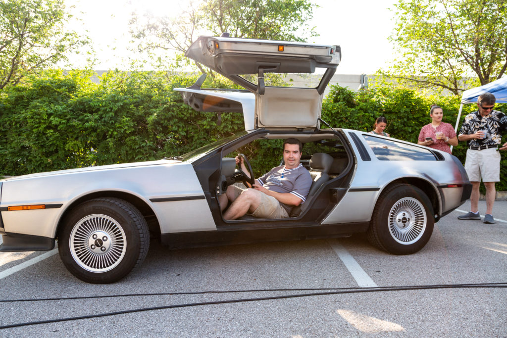 Casey Scott sits in a delorean with both gullwing doors open