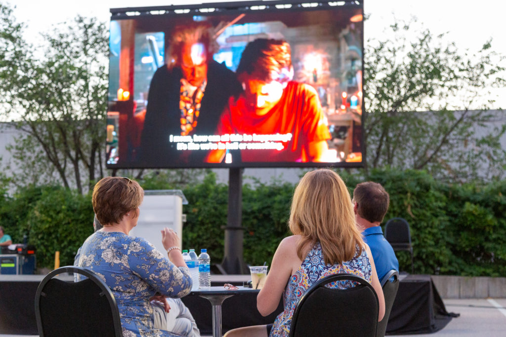 Three people seated around a small, round table watch Back to the Future 2 on the drive-in screen